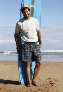 Beto in Badehose vor Surfbrett